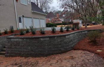 Stone wall and stairs leading to the garage driveway